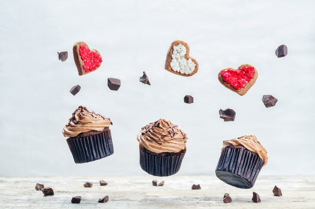 Flying chocolate cupcakes and cookies in the forms of heart